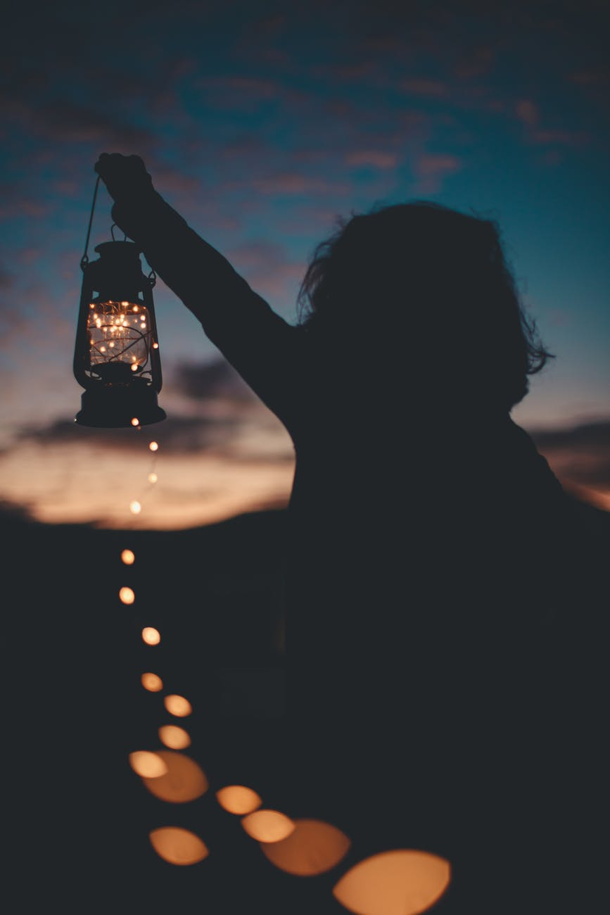 silhouette photo of person holding a lantern